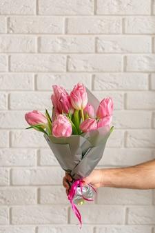 Man met boeket van mooie roze lente tulpen in de buurt van witte bakstenen muur.