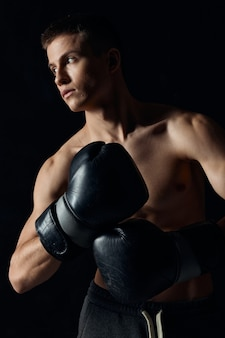 Man met bokshandschoenen naakt torso zwarte achtergrond bijgesneden weergave model fitness bodybuilder