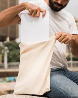 Man met boodschappentas gevuld met papier
