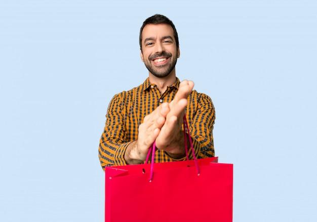 Man met boodschappentassen klappen na presentatie in een conferentie over geïsoleerde blauwe achtergrond