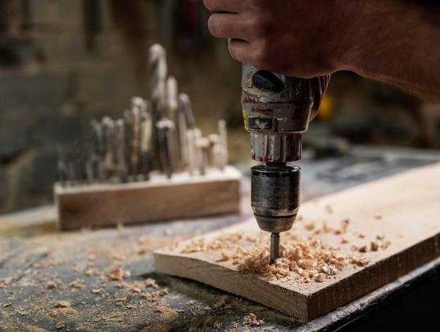 Man met boor die met hout werkt