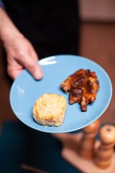 Man met bord met eten voor romantisch jubileum met vrouw in keuken gepensioneerde man in keuken met