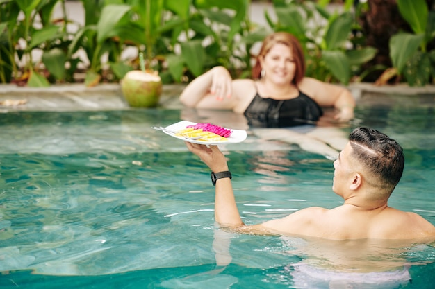 Man met bord met plakjes fruit naar zijn vrouw verfrissend in zwembad, uitzicht vanaf de achterkant