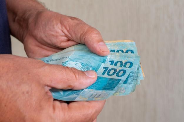 Man met braziliaans geld in zijn hand