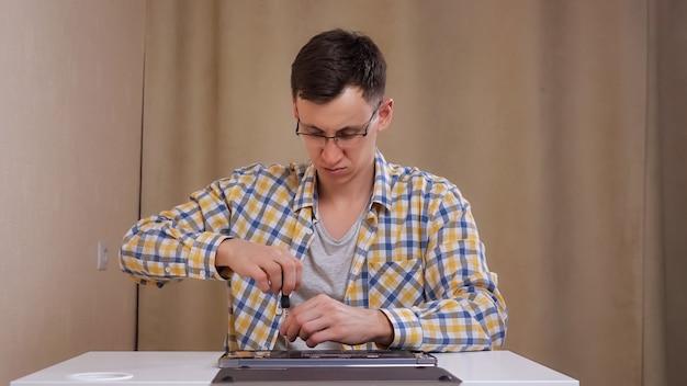 Man met bril demonteert een laptop terwijl hij aan een witte tafel zit
