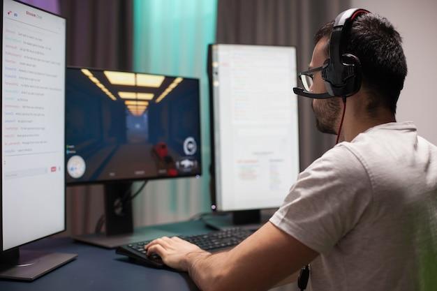 Man met bril die een koptelefoon draagt tijdens het spelen van schietspellen en het lezen van streamingchats op een installatie met twee schermen