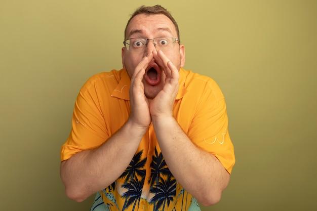 Man met bril die een oranje overhemd draagt dat schreeuwt of iemand belt met hnads in de buurt van de mond, verrast en bezorgd over groene muur staan