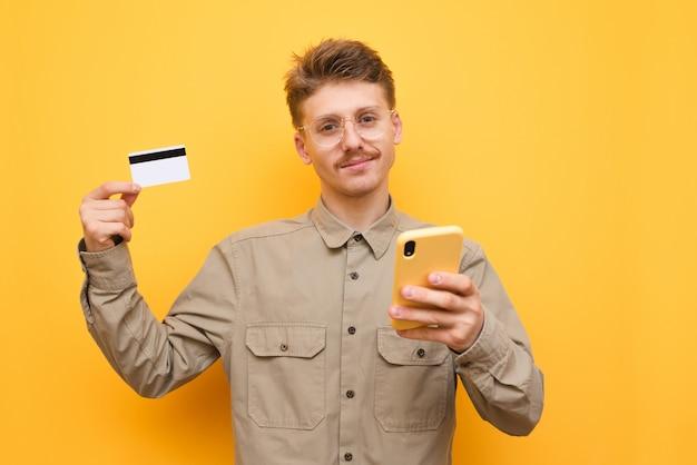 Man met bril en snor met creditcard en smartphone, camera kijken en glimlachen tegen geel