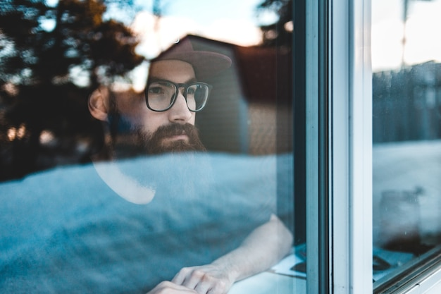 Man met bril kijkt door het raam