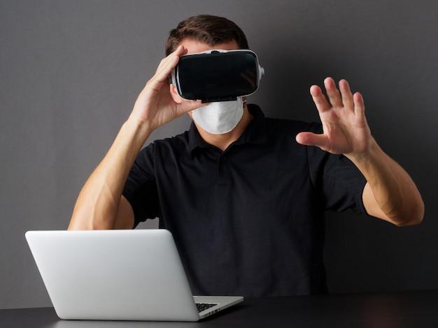 Man met bril van virtual reality met beschermend masker op zijn gezicht. concept blijf thuis. mensen beschermen tegen covid-19.