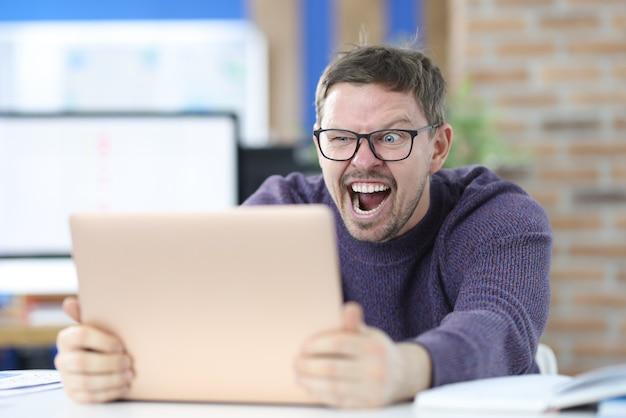 Man met bril voor zicht op zoek naar laptop. succesvol werkconcept