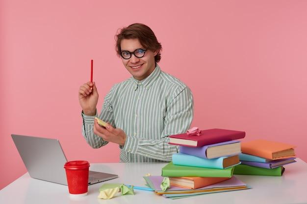 Man met bril zit bij de tafel en werkt met laptop, houdt een potlood in de hand, heeft een geweldig idee, kijkt naar de camera en glimlacht breed, geïsoleerd op roze achtergrond.
