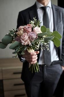 Man met bruidsboeket in handen, bruidegom maakt zich klaar in de ochtend voor de huwelijksceremonie