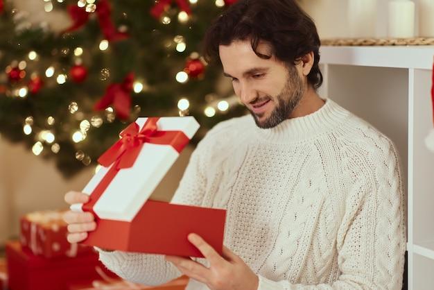 Man met cadeau in de geschenkdoos bij de kerstboom thuis