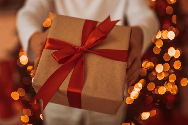 Man met cadeau in zijn hand op bokeh achtergrond