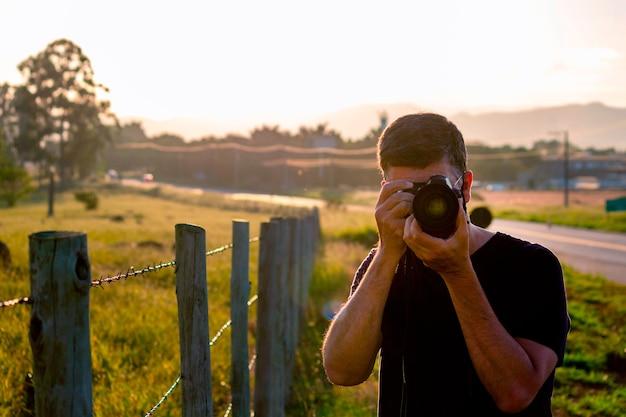 Man met camera fotograferen in het veld selectieve focus