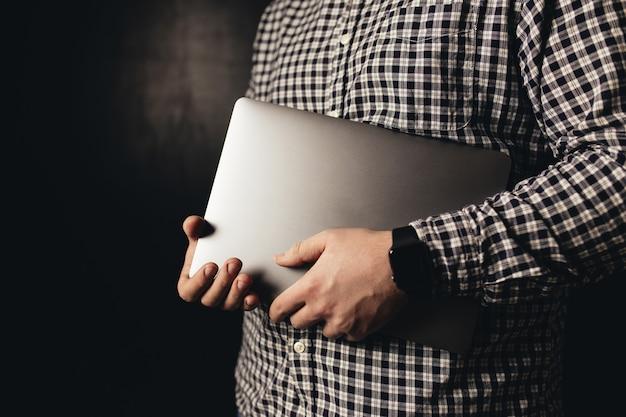 Man met casual kleding houdt gesloten laptop, zwarte onscherpe achtergrond