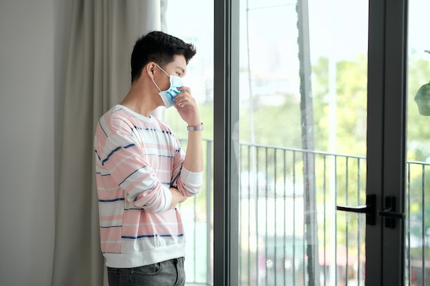 Man met chirurgisch masker kijkt uit zijn huisraam. coronavirus, covid-19 en quarantaineconcept.