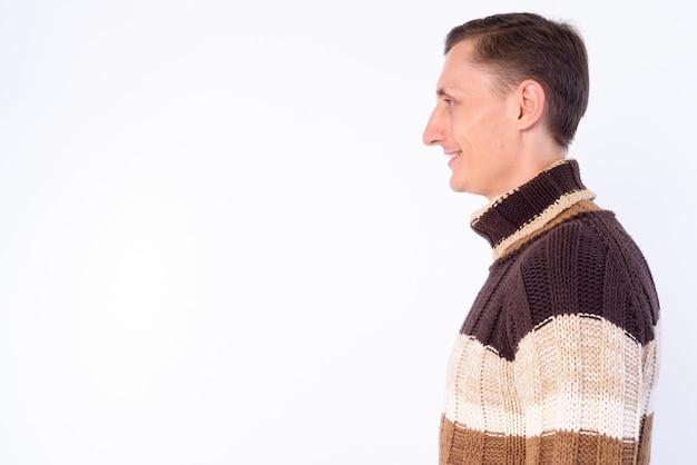 Man met coltrui klaar voor de winter geïsoleerd tegen witte muur