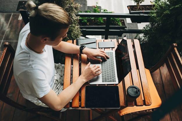 Man met creatieve kapsel zitten in casual zomerkleding aan houten plank café tafel met planten rond typen op laptop toetsenbord met gadgets die in de buurt van bovenaf