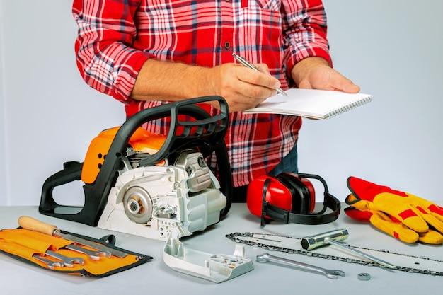 Man met dagboek notebook een pen in reparatiewerkplaats. reparatie van kettingzagen, gereedschap op benzine.