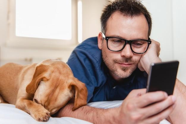 Man met de hond met behulp van slimme telefoon op het bed