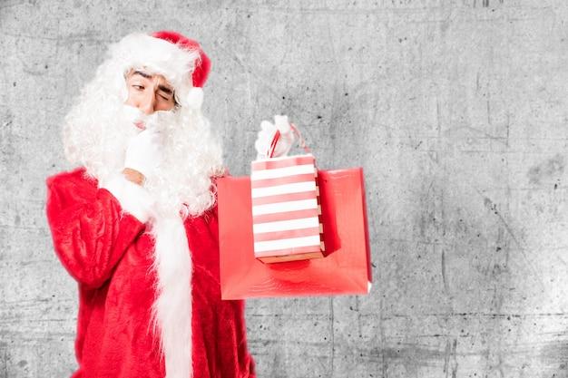 Man met de kerstman kostuum bedrijf boodschappentassen