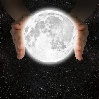 Man met de maan in de handen tegen de muur van de melkweg. Premium Foto