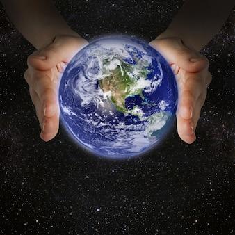 Man met de planeet aarde in de handen tegen de muur van de melkweg. Premium Foto