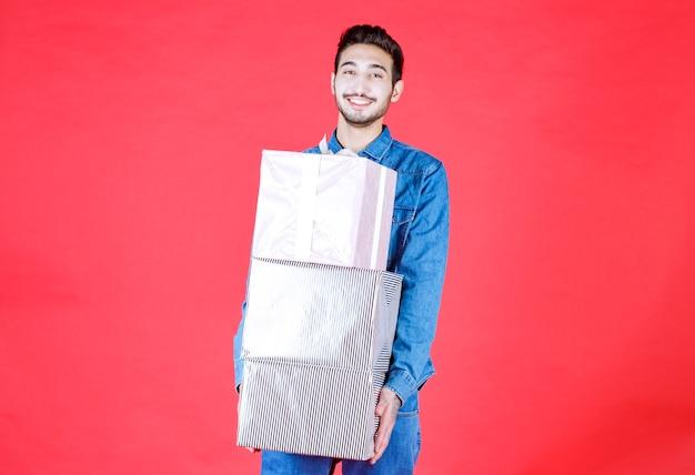 Man met de voorraad zware zilveren geschenkdozen op de rode muur.