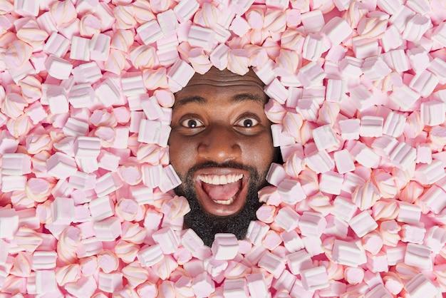 Man met dikke baard ziet er vrolijk uit houdt mond open verdronken in zoete smakelijke marshmallow geniet van het eten van smakelijke lekkernijen