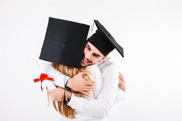 Man met diploma omhelst vrouw