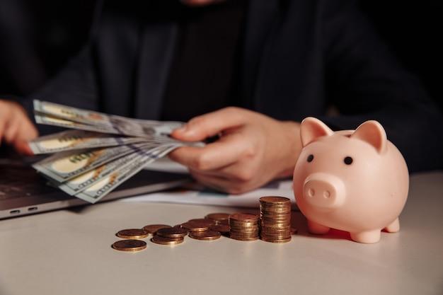 Man met dollar biljetten in zijn hand werken met behulp van laptop, roze spaarvarken met munten voor hem. investeringen en bedrijfsconcept