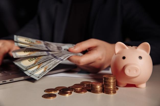 Man met dollar biljetten in zijn hand werken met behulp van laptop, spaarvarken met munten voor hem. investeringen en bedrijfsconcept.