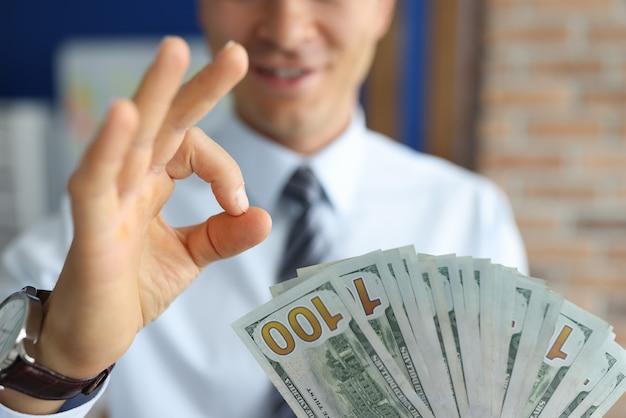 Man met dollarbiljetten toont ok