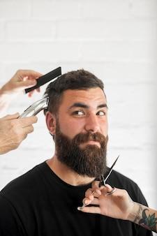 Man met donker haar en lange baard wordt verzorgd en bijgesneden