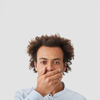 Man met donkere huid, heeft ernstige uitdrukking, bedekt de mond met de hand, probeert stom te zijn en geen geruchten te verspreiden