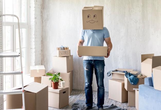 Man met doos boven het hoofd tijdens het inpakken om te verhuizen