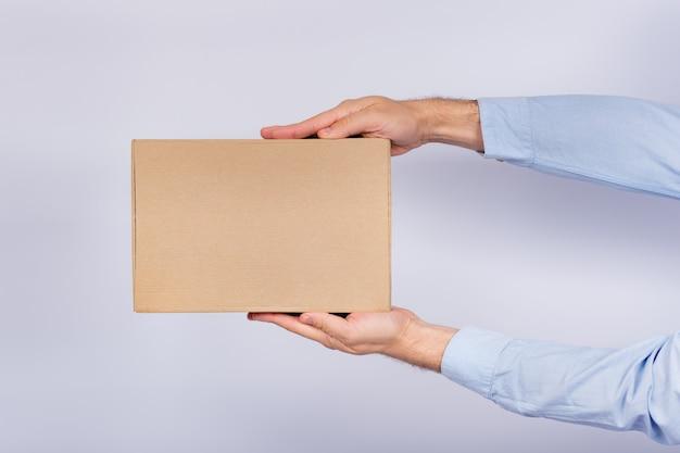 Man met doos op arm's length. kartonnen doos. levering van pakketten. zijaanzicht.