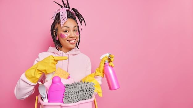 Man met dreadlocks in vrijetijdskleding poseert in de buurt van wasbak met wasmiddelen reinigt kamerpunten weg op lege ruimte op roze