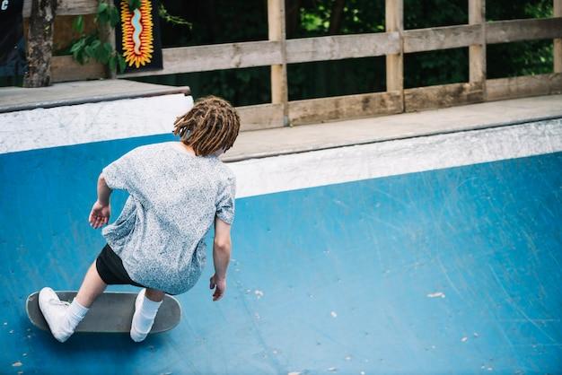 Man met dreadlocks op skateboard