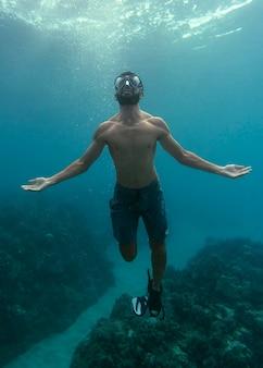 Man met duikuitrusting die in de oceaan zwemt