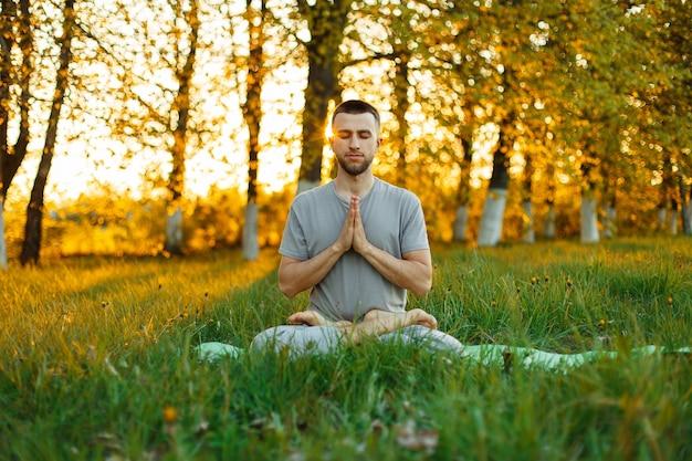 Man met een baard beoefenen van yoga op de natuur bij zonsondergang. gezonde levensstijl