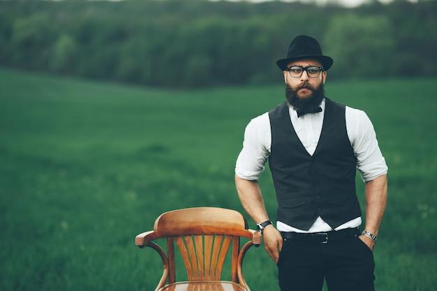 Man met een baard, denkend in het veld bij stoel