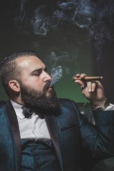 Man met een baard en een groen pak, sigaren roken en roken in profiel.