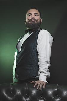 Man met een baard, gekleed in een vest en vlinderdas, staande op een bank.