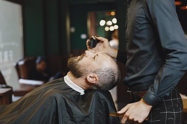 Man met een baard. kapper met een klant. man met een kam en een schaar