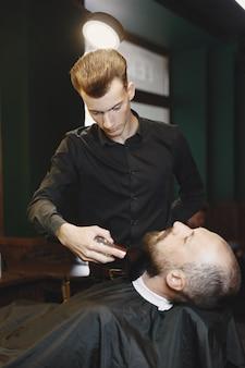 Man met een baard. kapper met een klant. man met een penseel.