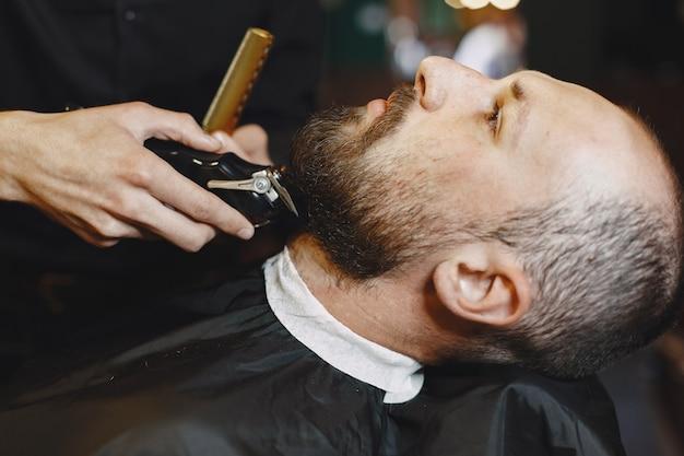 Man met een baard. kapper met een klant. man met een scheerbeurt.