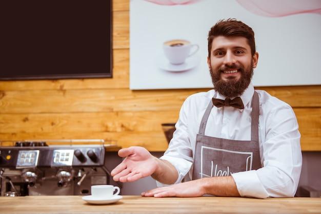 Man met een baard staat achter de toonbank met de gebrouwen koffie.